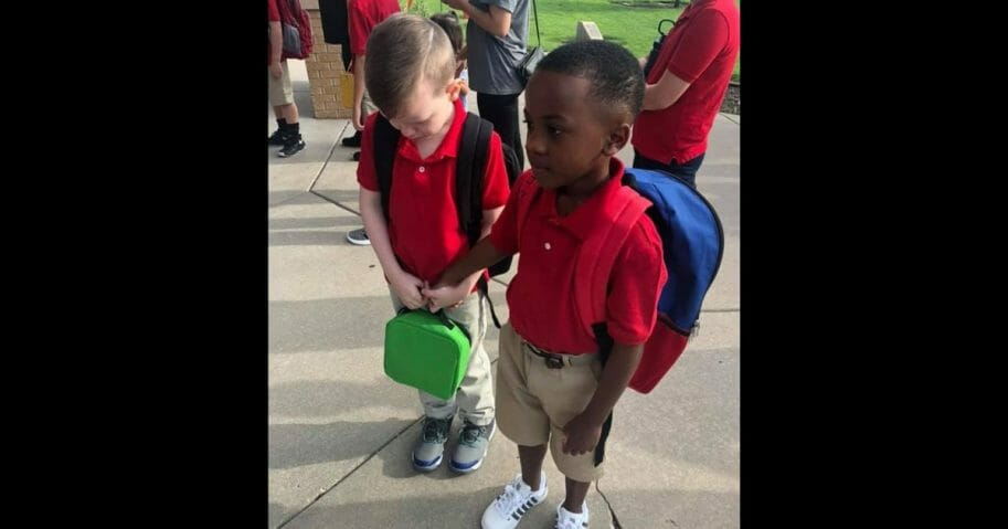 Two boys hold hands on first day of school.