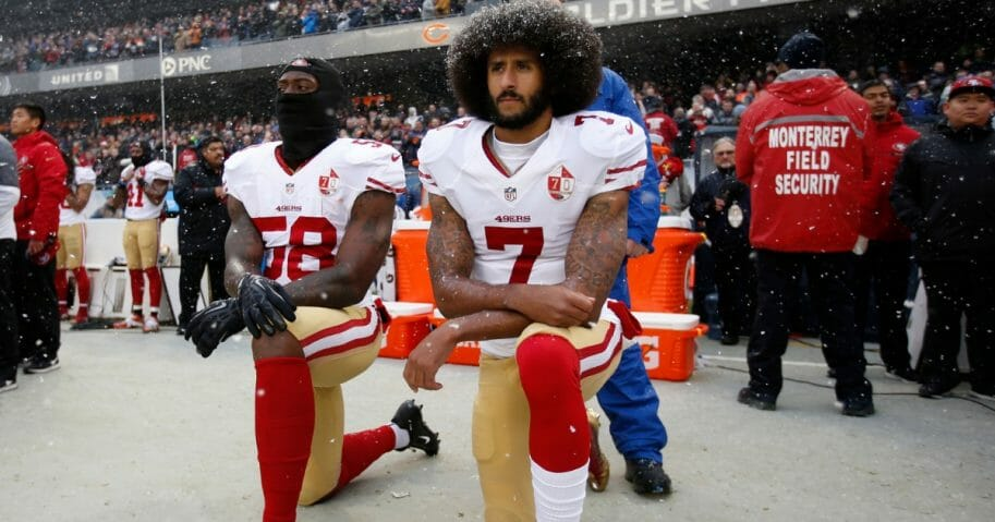 Eli Harold #58 and Colin Kaepernick #7 of the San Francisco 49ers kneel on the sideline, during the anthem, prior to the game against the Chicago Bears at Soldier Field on Dec. 4, 2016, in Chicago, Illinois.