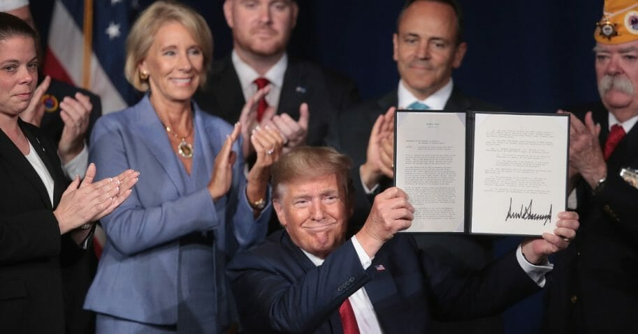 President Donald Trump signs a proclamation that will eliminate student loan debt for qualifying disabled veterans following a speech at the American Veterans' 75th National Convention at the Galt House on Aug. 21, 2019, in Louisville, Kentucky.