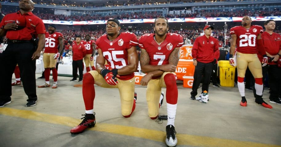 Colin Kaepernick, right, and Eric Reid of the San Francisco 49ers kneel during the national anthem.