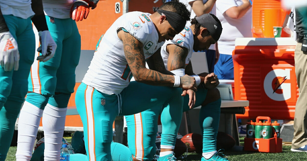 Kenny Stills #10 and Albert Wilson #15 of the Miami Dolphins kneel during the national anthem prior to their game against the New England Patriots at Gillette Stadium on Sept. 30, 2018, in Foxborough, Massachusetts.