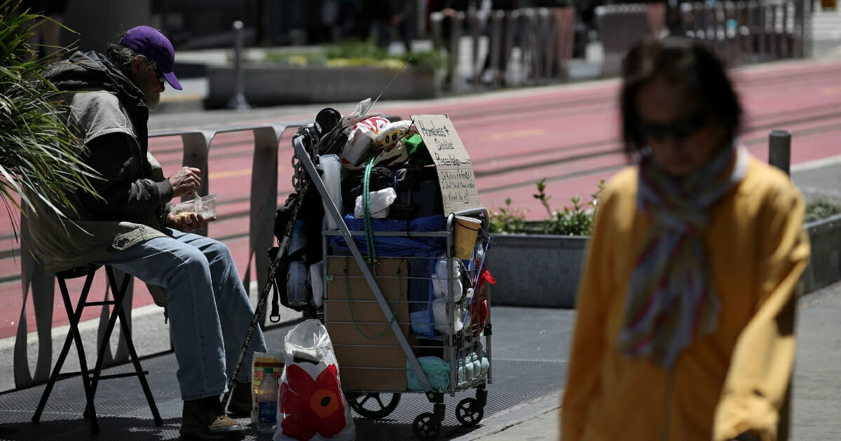 A pedestrian walks by a homeless man who is begging for money on May 17, 2019, in San Francisco, California.