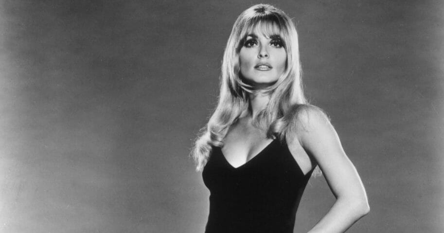Studio portait of American actor Sharon Tate (1943 - 1969) posing in a black grown with her hand on her hip.