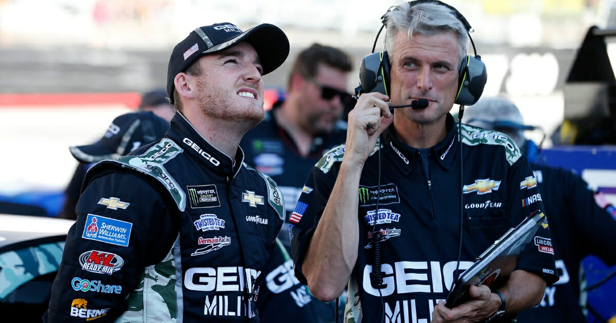 Ty Dillon, driver of the #13 GEICO Military Chevrolet, and crew chief Matt Borland stand on the grid during qualifying for the Monster Energy NASCAR Cup Series Bass Pro Shops NRA Night Race at Bristol Motor Speedway on Aug. 16, 2019, in Bristol, Tennessee.