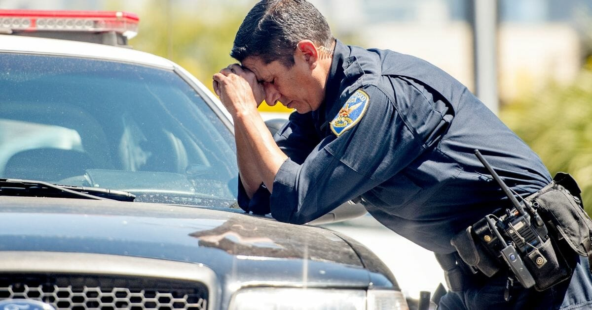 A police officer reacts at the scene where a gunman shot and killed multiple people including himself at a UPS facility in San Francisco, California on June 14, 2017.