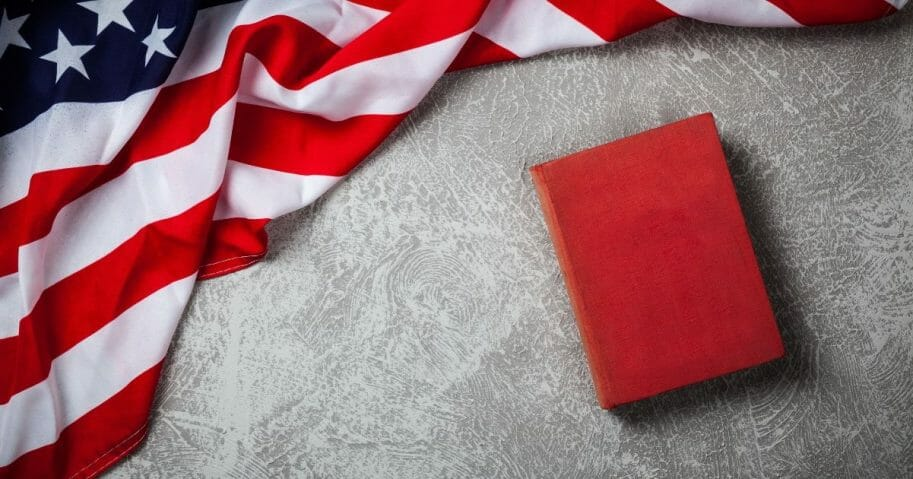 A red book sits on a table near an American flag.