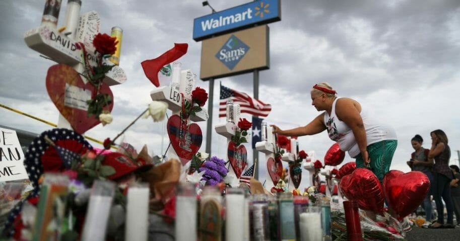 A woman touches a cross at a makeshift memorial for victims outside Walmart, near the scene of a mass shooting which left at least 22 people dead, on August 6, 2019 in El Paso, Texas.