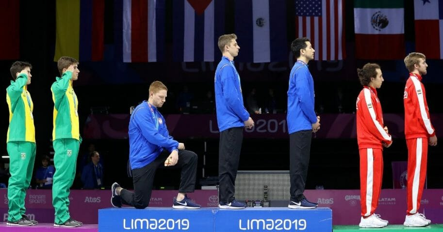 Gold medalist Race Imboden of United States takes a knee during the National Anthem Ceremony in the podium of Fencing Men's Foil Team Gold Medal Match Match on Day 14 of Lima 2019 Pan American Games at Fencing Pavilion of Lima Convention Center on August 09, 2019 in Lima, Peru.