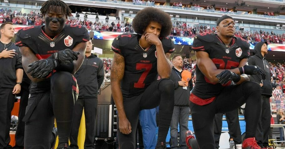 Members of the San Francisco 49ers kneel in protest during the national anthem prior to their NFL game against the Arizona Cardinals on October 6, 2016.