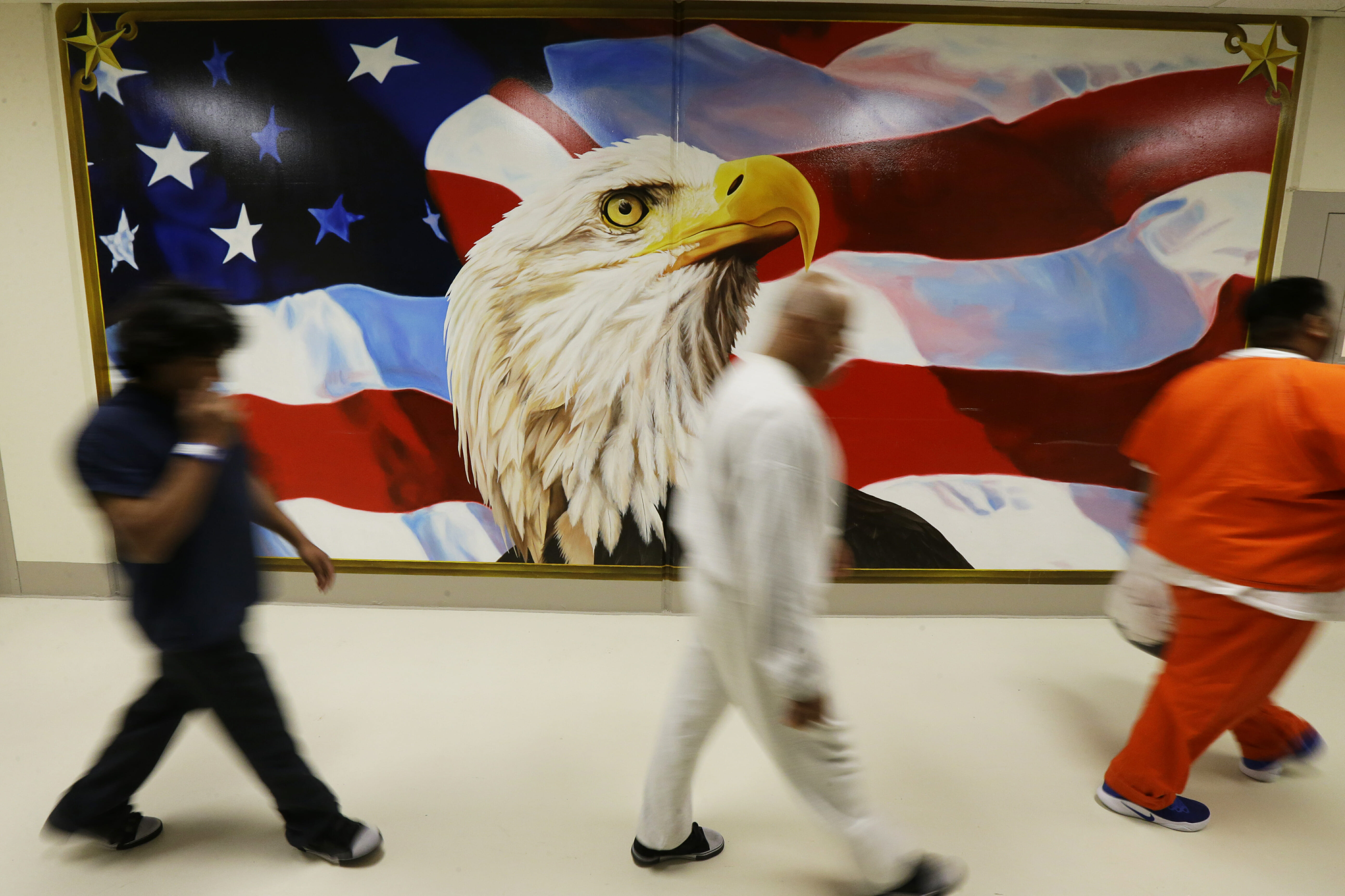In June 21, 2017, file photo, detainees walk past a mural in the Northwest Detention Center in Tacoma, Washington, during a media tour of the facility.
