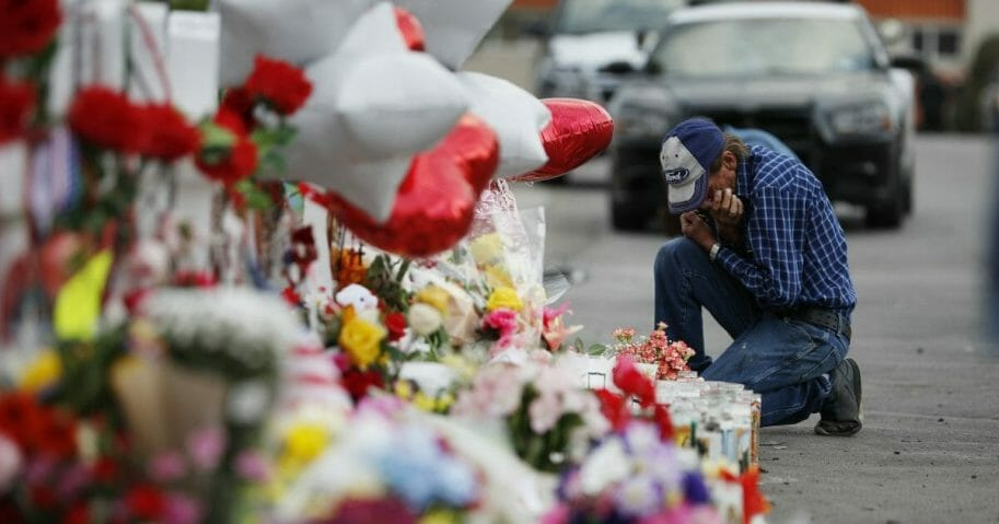 A man cries beside a cross at a makeshift memorial near the scene of a mass shooting at a shopping complex Tuesday, Aug. 6, 2019, in El Paso, Texas.