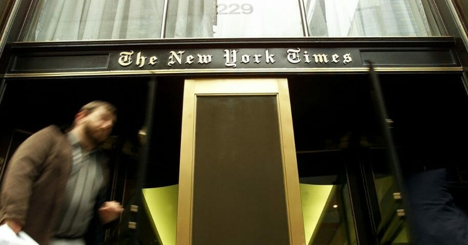 A pedestrian walks past the entrance to The New York Times building
