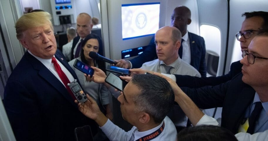 President Donald Trump speaks to the media aboard Air Force One while flying between El Paso, Texas and Joint Base Andrews in Maryland, August 7, 2019.