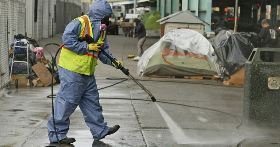 A city worker uses a power washer to clean the sidewalk by a tent city along Division Street in San Francisco on Feb. 26, 2016.