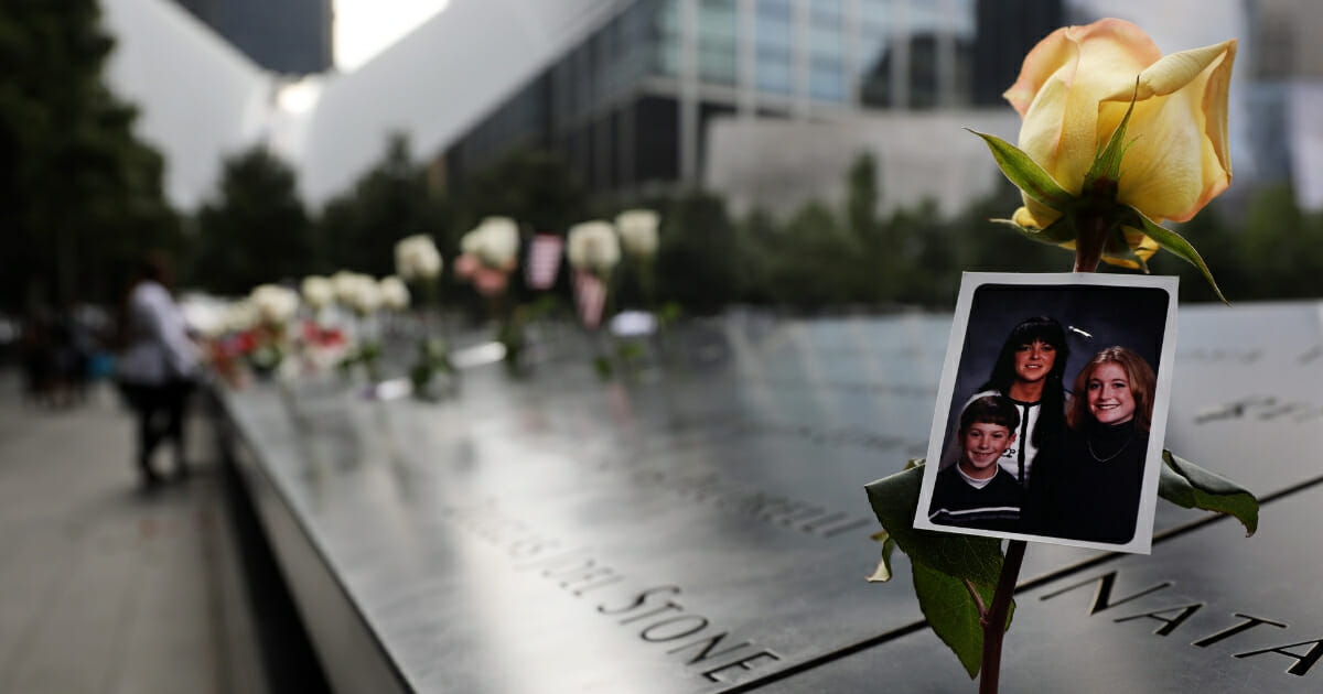 A family photo is seen among the names on the National September 11 Memorial during a commemoration ceremony the morning of Sept. 11, 2019, honoring the victims of the terrorist attacks 18 years ago.