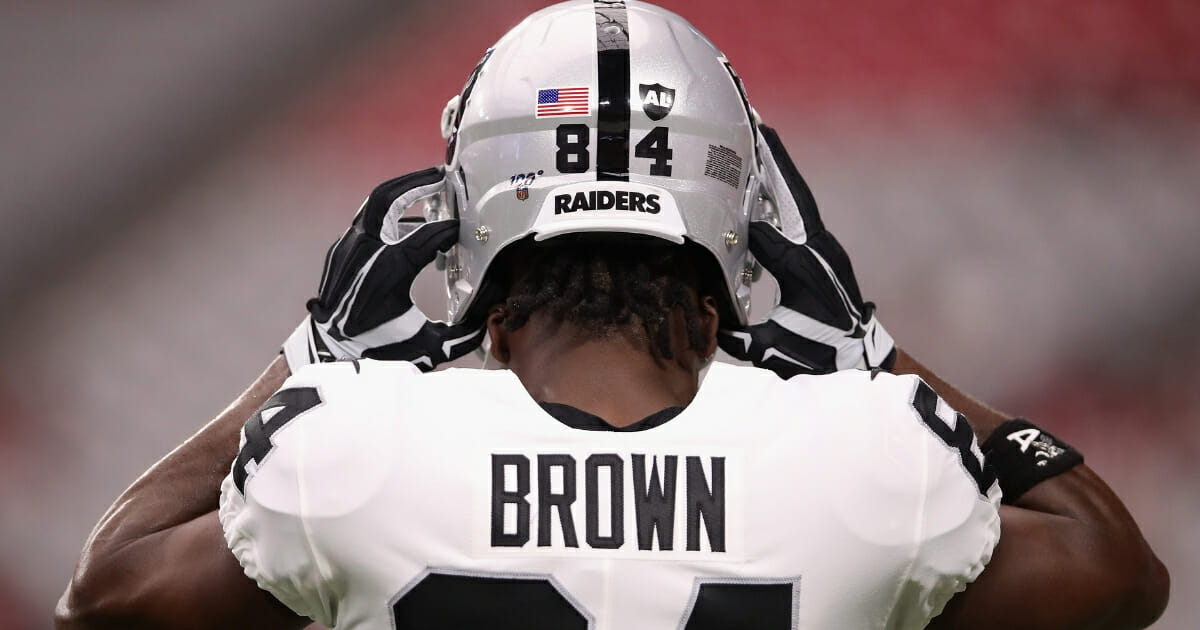 Wide receiver Antonio Brown #84 of the Oakland Raiders adjusts his helmet before the NFL preseason game against the Arizona Cardinals at State Farm Stadium on Aug. 15, 2019, in Glendale, Arizona.