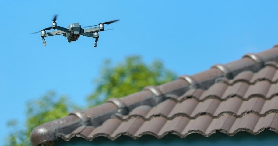 A drone flies near the roof of a house.