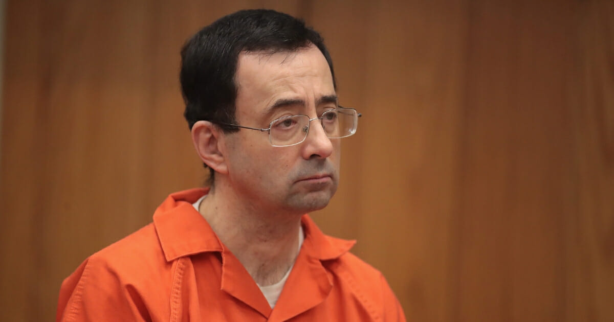 Larry Nassar stands as he is sentenced by Judge Janice Cunningham for three counts of criminal sexual assault in Eaton County Circuit Court on Feb. 5, 2018, in Charlotte, Michigan.