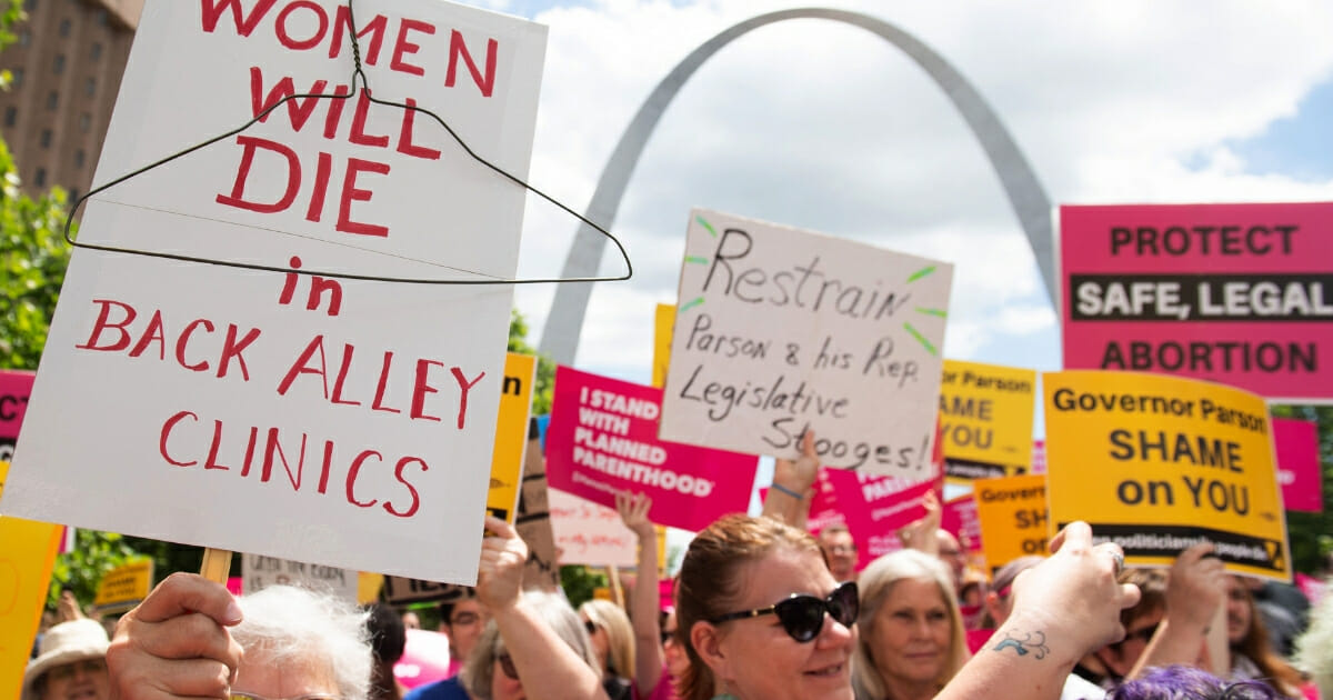 Protesters hold signs as they rally in support of Planned Parenthood near the Gateway Arch in St. Louis, Missouri on May 30, 2019.