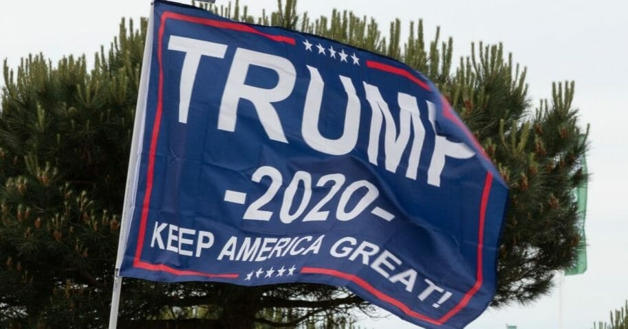 A man holds a sign saying trump 2020 during the d day 75 celebrations in Portsmouth