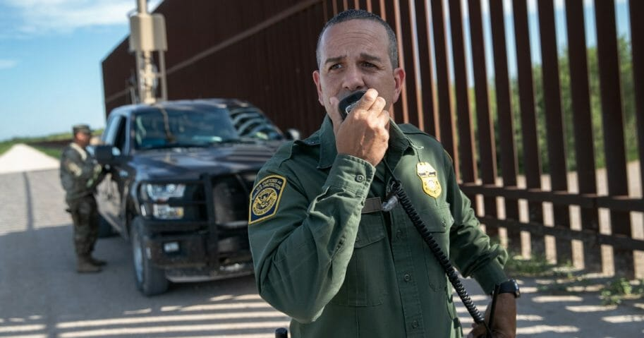 Border Patrol agent Carlos Ruiz spots a pair of undocumented immigrants while coordinating with active duty U.S. Army soldiers near the U.S.-Mexico border fence on Sept. 10, 2019, in Penitas, Texas.