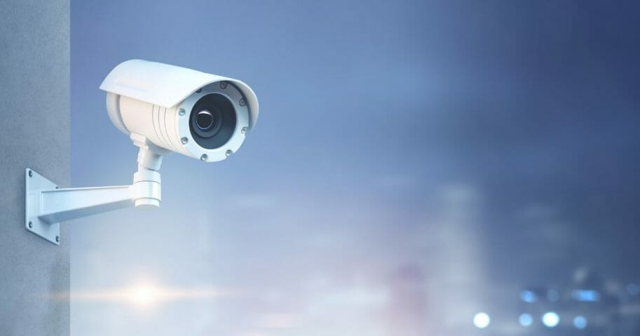 Stock image of a surveillance camera on a wall.