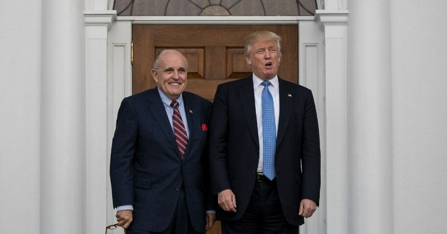 Former New York City mayor Rudy Giuliani stands with then-president-elect Donald Trump before their meeting at Trump International Golf Club, Nov. 20, 2016, in Bedminster Township, New Jersey.