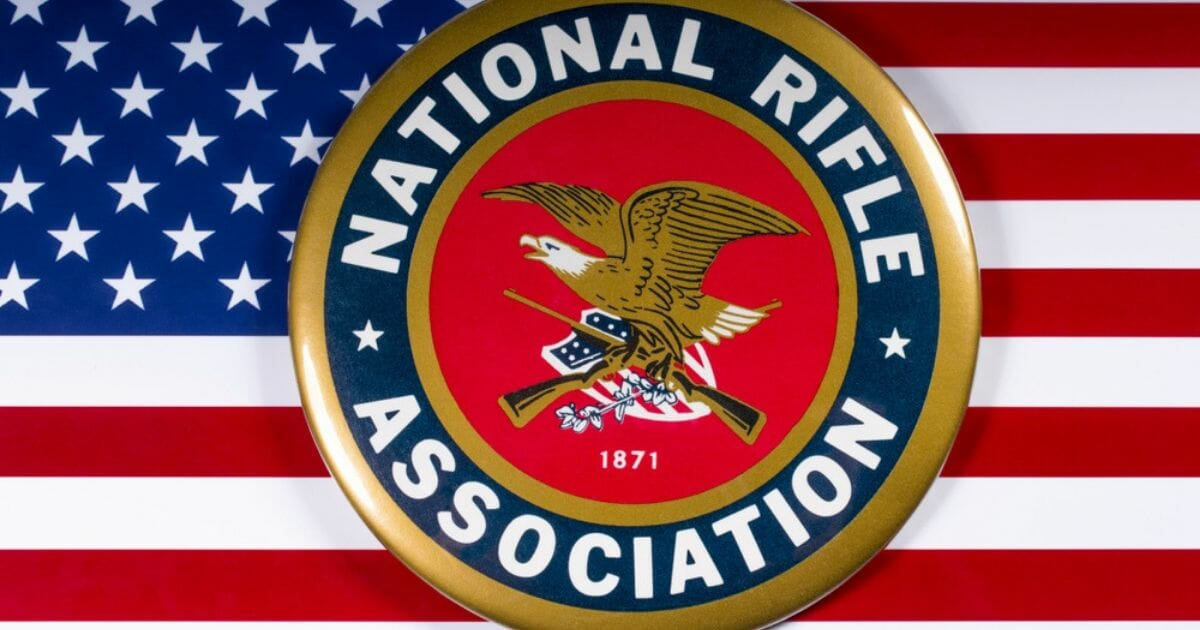 The symbol of the National Rifle Association portrayed with the U.S. flag.
