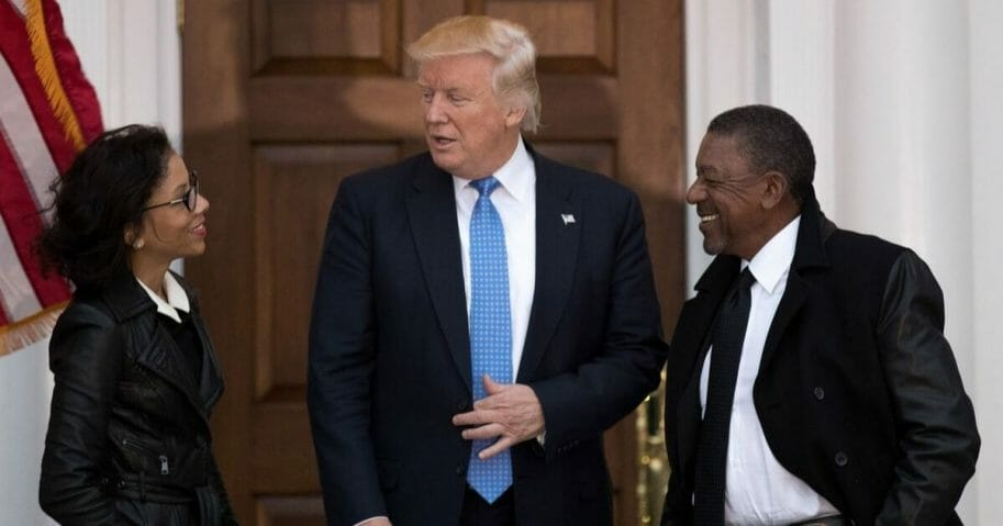 President-elect Donald Trump greets Robert Johnson, the founder of Black Entertainment Television, and his wife Lauren Wooden as they arrive for a meeting with president-elect Donald Trump at Trump International Golf Club, Nov. 20, 2016 in Bedminster Township, New Jersey.