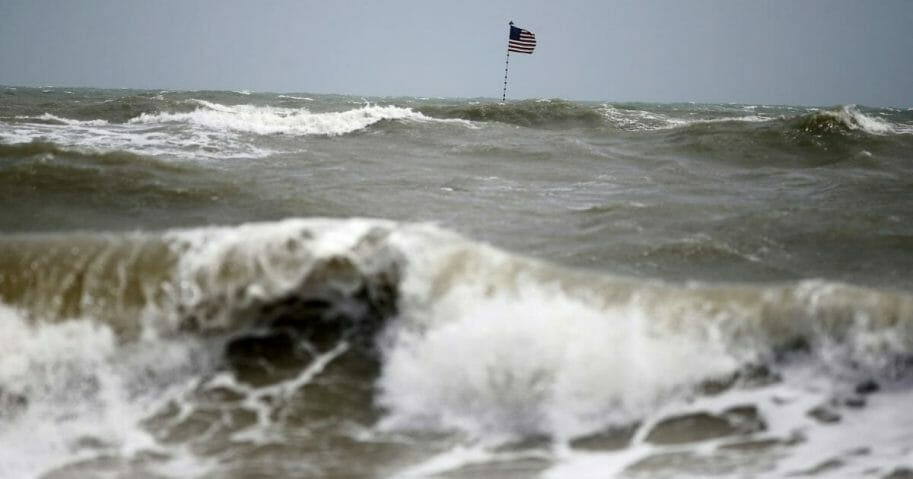 Waves crash in front of an American flag that is planted on a jetty during a high surf from the Atlantic Ocean