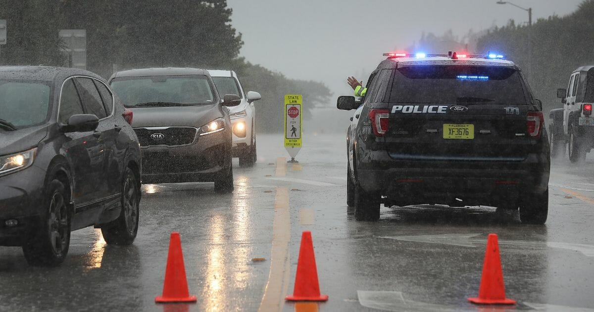 A Highland Beach police officer sits in his vehicle to check id's of people in cars as he only allows residents to enter the Highland Beach area as Hurricane Dorian continues to make its way toward the Florida coast.