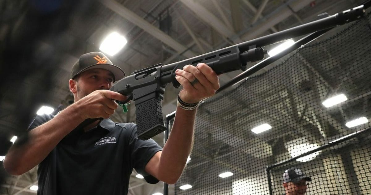 An attendee participates in a gun reloading competition at the Remington booth during the NRA Annual Meeting & Exhibits at the Kay Bailey Hutchison Convention Center.