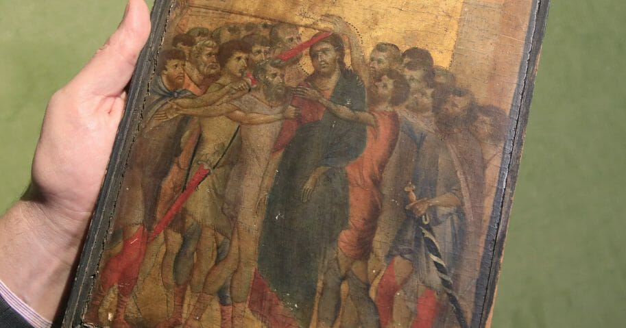 In this Sept. 24, 2019, file photo, art expert Stephane Pinta points to a 13th-century painting by Italian master Cimabue in Paris.