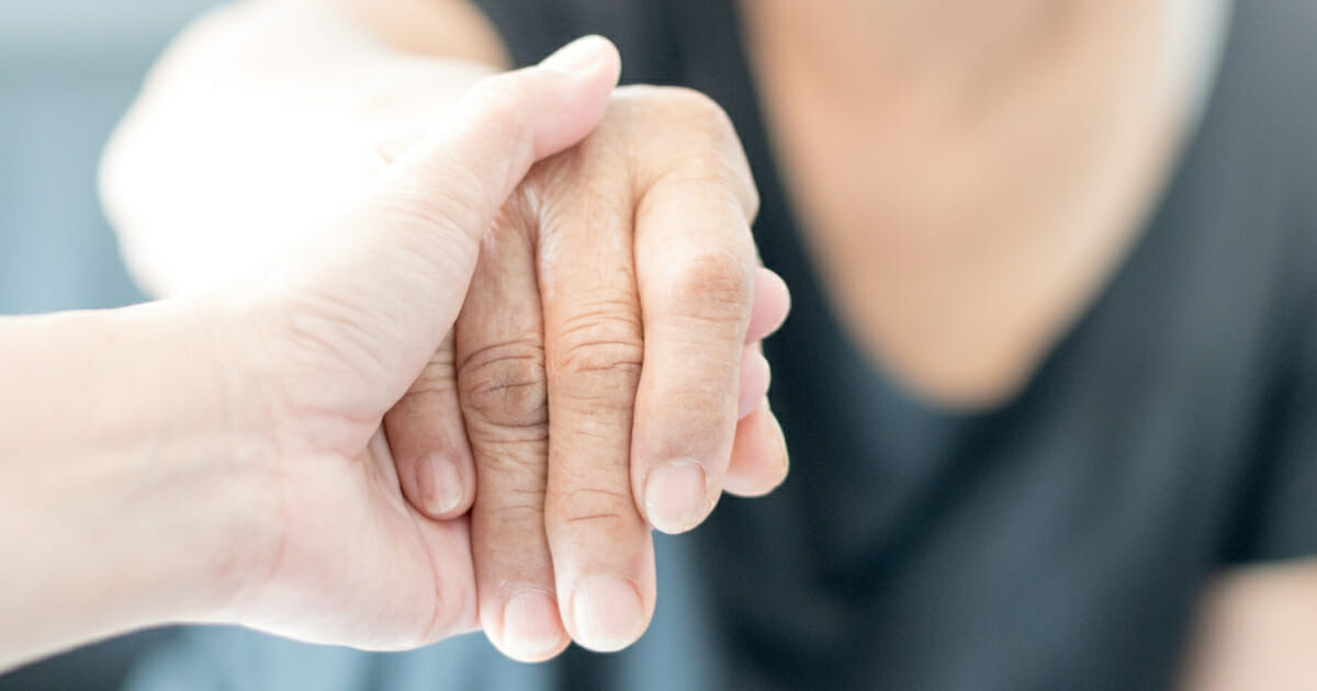 A young hand holds an elderly hand.