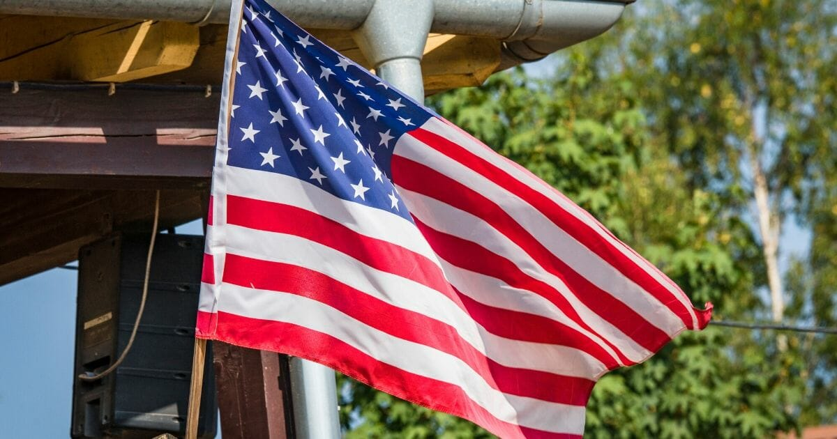 American flag on a porch outside a small cabin in the summer.