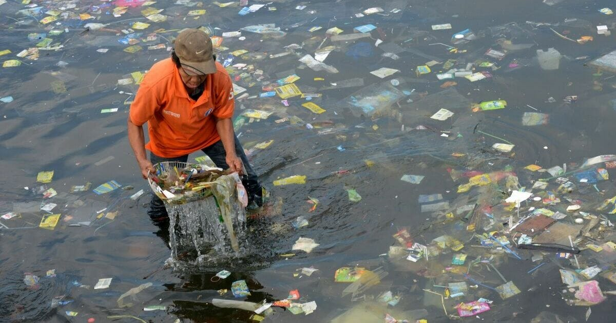 A volunteer picks trash out of Manila Bay.