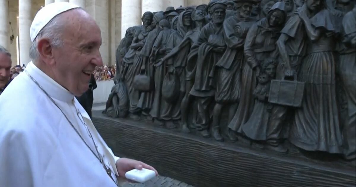 Pope Francis looks over a statue of refugees.