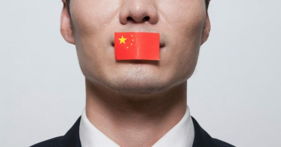 Stock photo of a Chinese flag covering up a man's mouth.