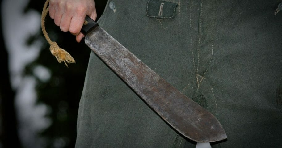 A stock photo of a man holding a machete.
