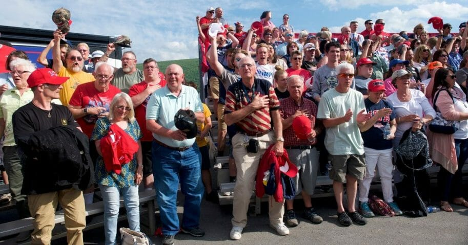 """Supporters stand for the Pledge of Allegiance before U.S. President Donald J. Trump held a """"MAGA"""" rally at the Williamsport Regional Airport."""