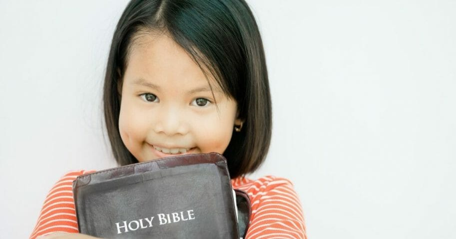 Stock image of a child holding a Bible.