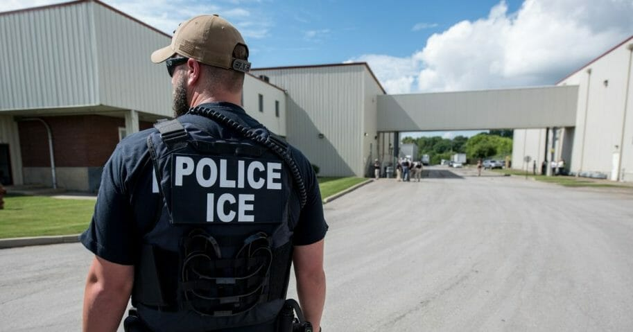 An Immigration and Customs Enforcement special agent prepares to arrest illegal aliens at a meat wholesaler in Ohio in June.