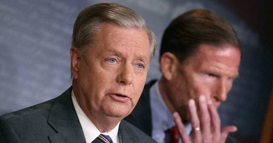 Senate Judiciary Chairman Lindsey Graham of South Carolina speaks while Sen. Richard Blumenthal of Connecticut listens during a news conference to discuss the introduction of bipartisan legislation to impose severe sanctions on Turkish officials in response to their incursion into northern Syria, on Capitol Hill on Oct. 17, 2019, in Washington, D.C.
