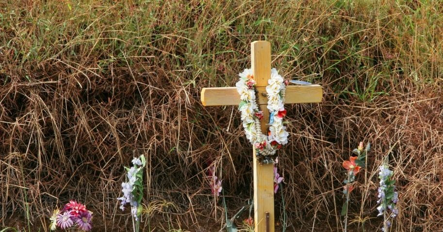 Stock image of a roadside cross on a highway set up as a memorial.