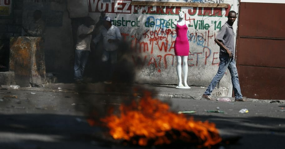 A man walks past a burning barricade during anti-government protests in Port-au-Prince, Haiti, on, Oct. 11, 2019.