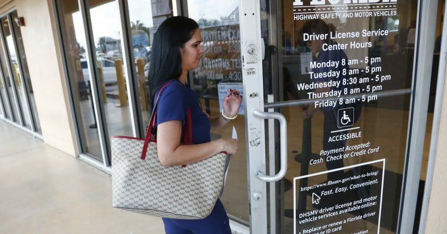A woman enters a Florida Highway Safety and Motor Vehicles drivers license service center, Tuesday, Oct. 8, 2019, in Hialeah, Fla.