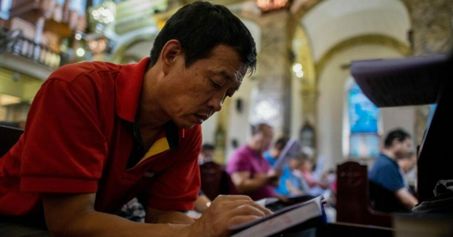 A man reads a bible during a mass at the South Cathedral in Beijing.