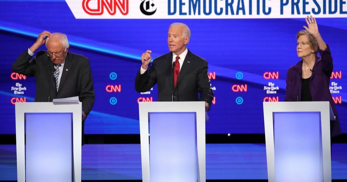 Sen. Bernie Sanders, former Vice President Joe Biden, and Sen. Elizabeth Warren react during the Democratic Presidential Debate at Otterbein University on Oct. 15, 2019 in Westerville, Ohio.