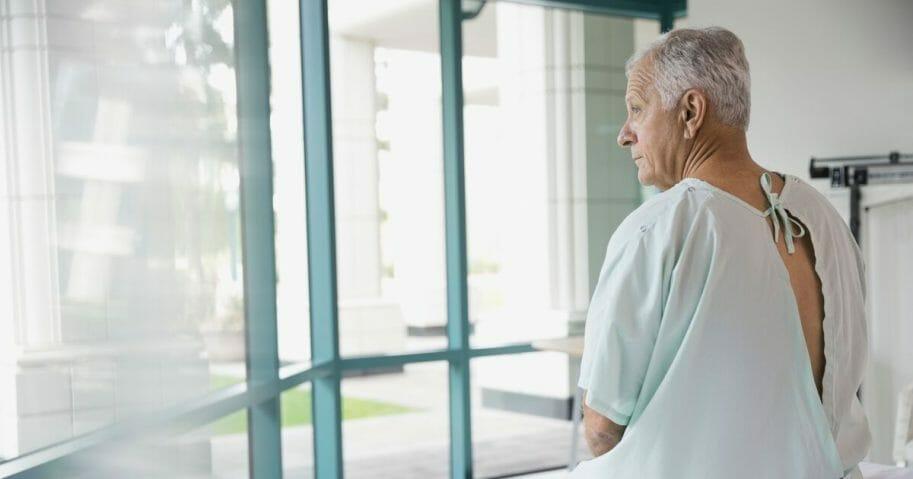 Senior patient sitting on hospital bed.
