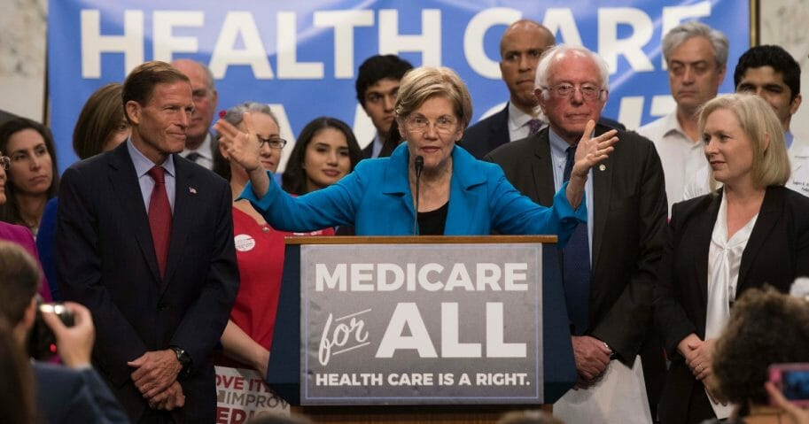 Senator Elizabeth Warren center, a Democrat from Massachusetts, speaks with Senator Bernie Sanders, second from the right, of Vermont as they discusses Medicare for All legislation on Capitol Hill in Washington, D.C., on Sept. 13, 2017.
